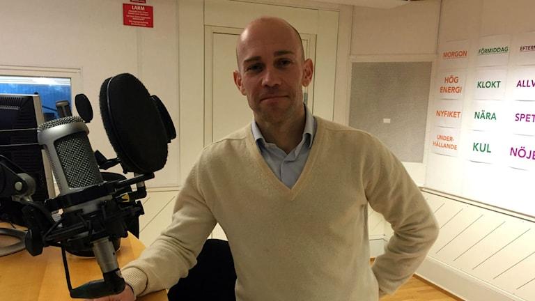 Personlige tränaren Matt Richardson har en vit tröja med blå skjort under och står lutad mot studiobordet i radiostudion.
