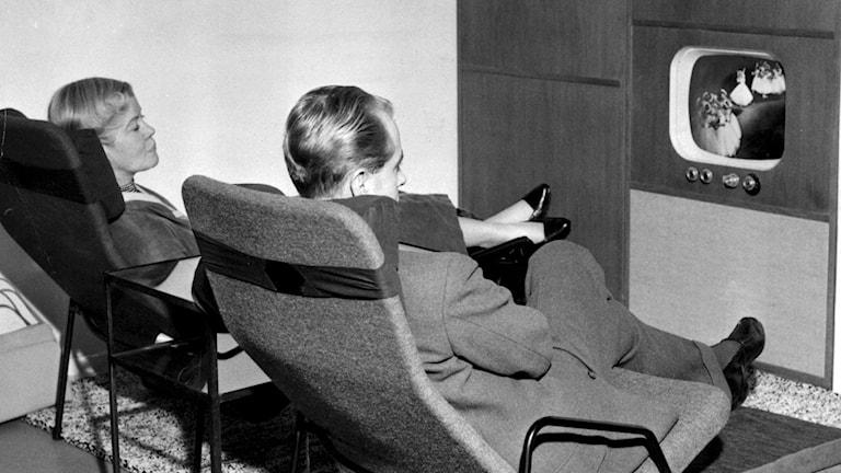 TV-tittare i TV-fåtöljer. Par bekvämt tillbakalutade framför TV-möbel à la 50-tal.