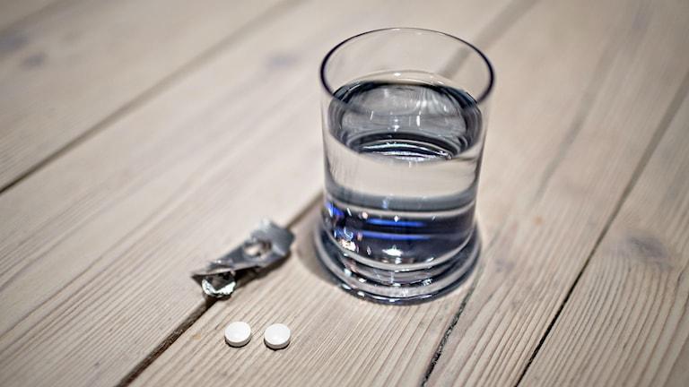 Medicin och glas med vatten