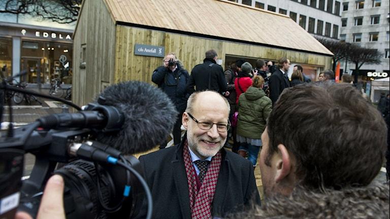 Stefan Attefall intervjuas framför ett Attefallshus.