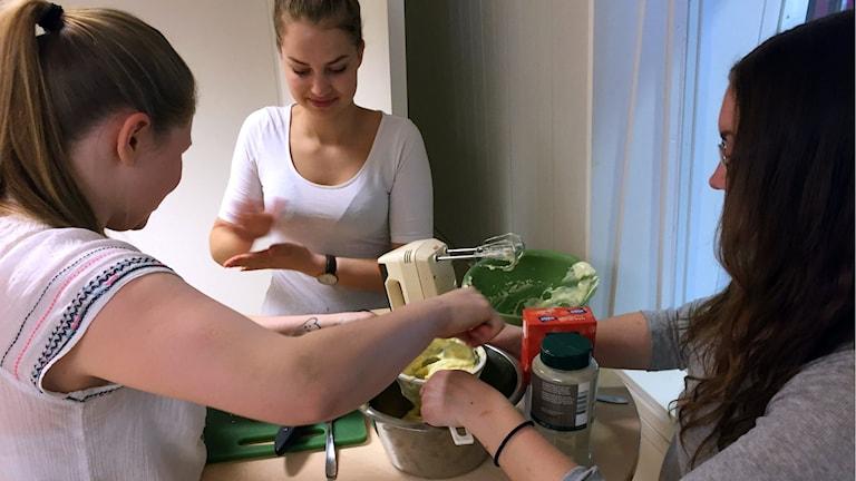 Finalisterna Linnea, Elina och Malin lagar mat tillsamamns i studion.