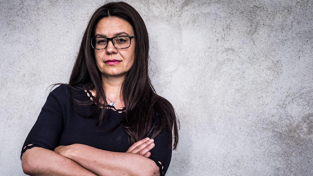 Kvinna med mörkt, långt hår och glasögon med mörka bågar. Står lutad mot en ljus vägg och har armarna i kors över bröstet.