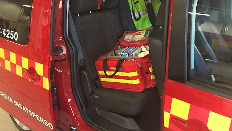 En öppen sjukvårdsväska står i baksätet på en brandbilsröd skåpbil. I väskan finns utrustning för hjälp vid hjärtstopp.