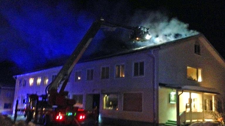 Kraftig rökutveckling från taket på ett vitt flerfamiljshus. En stegbil från räddningstjänsten står framför huset och det är mörkt ute.