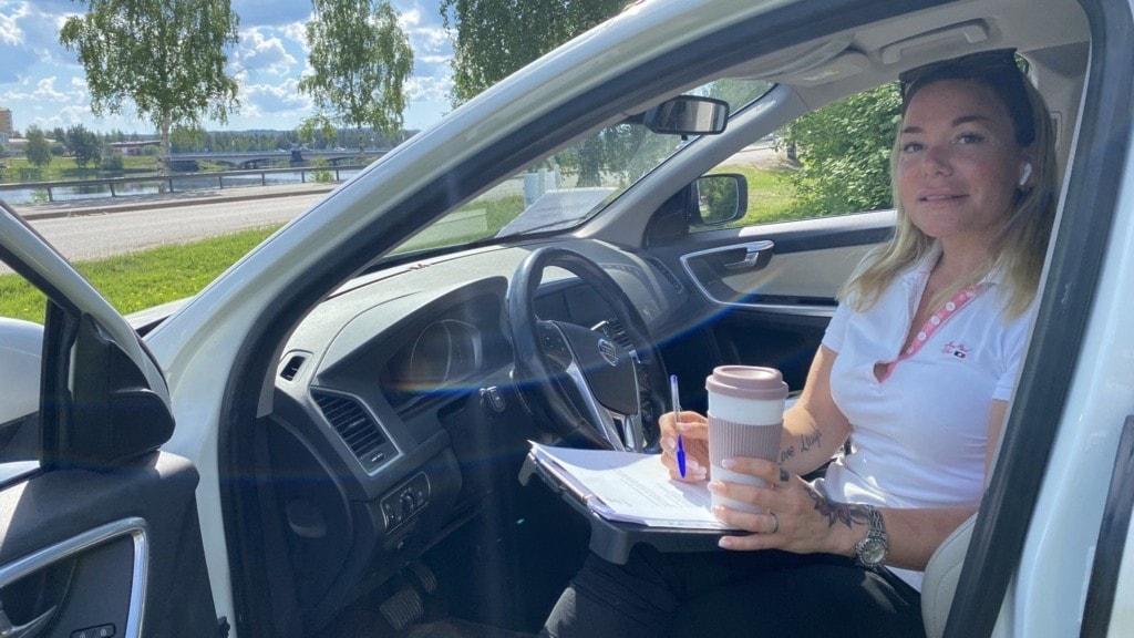 Ung kvinna sitter i förarsätet på en bil med dörren öppen. Hon har Penna, block och en take away-mugg i händern.