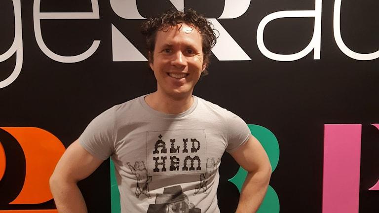 Erik Campano poserar framför sverigesradio-loggan