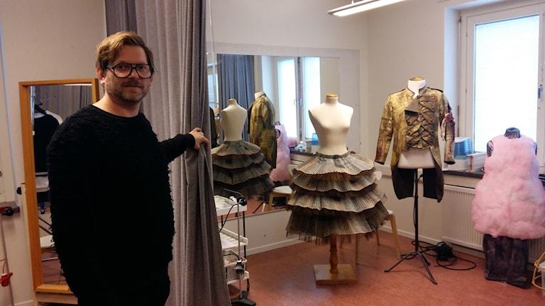 Designer Marcus Olsson framför tre av kostymerna som kommer synas på scenen till operan Faust, varav en av dem är en sockervaddsklänning. Foto: Linnea Hedelilja