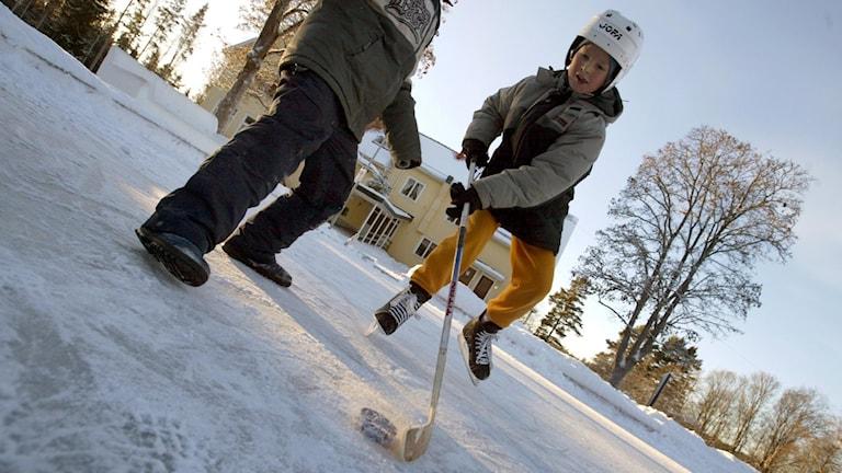 Två barn spelar ishockey utomhus.