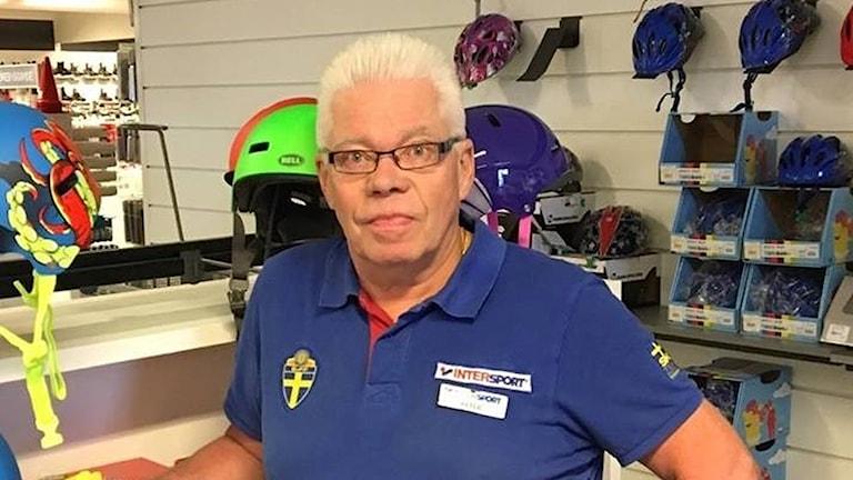 Peter Henriksson står bland en massa cykelhjälmar