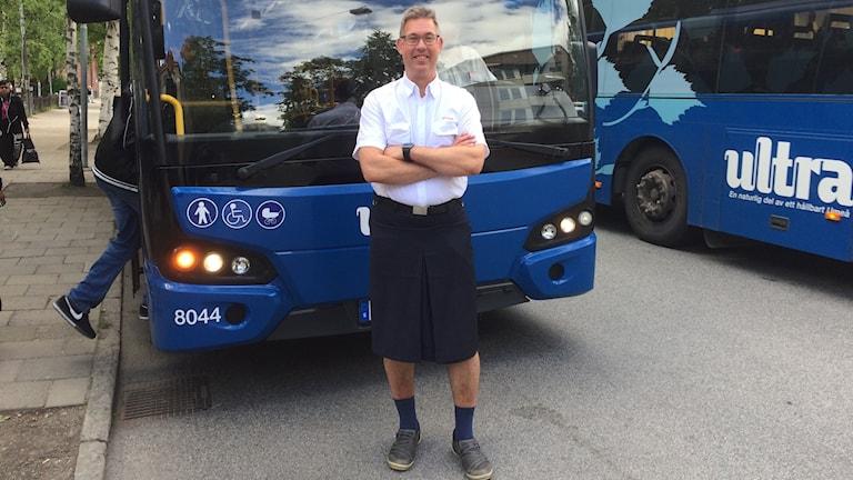 Man i kjol framför buss i busschaufförklädsel