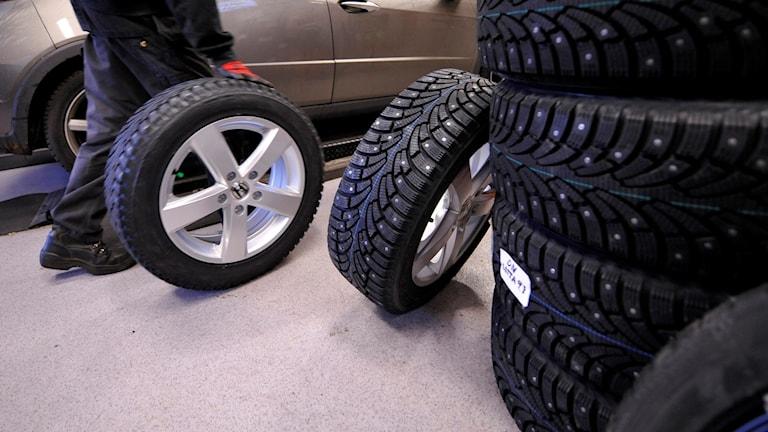 Några däck som ligger på hög och en person som rullar ett däck på aluminiumfälg