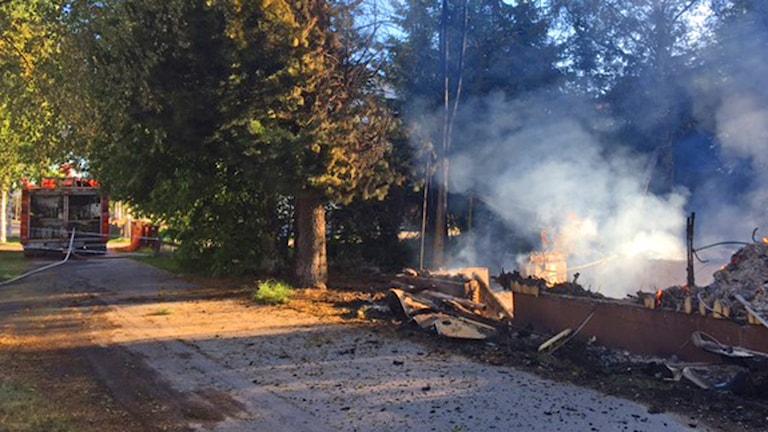 Baksidan av en brandbil intill rykande rester av ett nedbrunnet huss.
