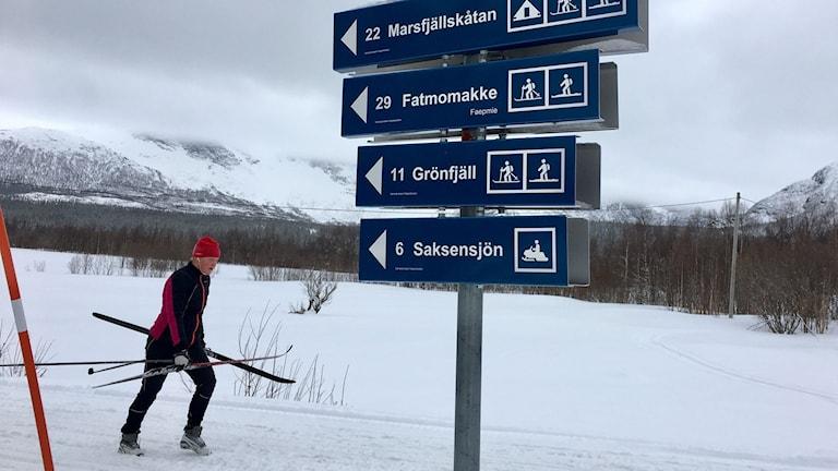Man med skidor i händerna går efter skoterspår. I bakgrunden fjäll.