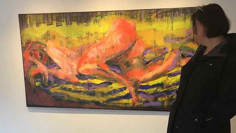 Ann-Catrine Eriksson vid stor tavla på naken kvinna i giftiga neonfärger Foto: Pia Diaz Bergner/Sveriges Radio