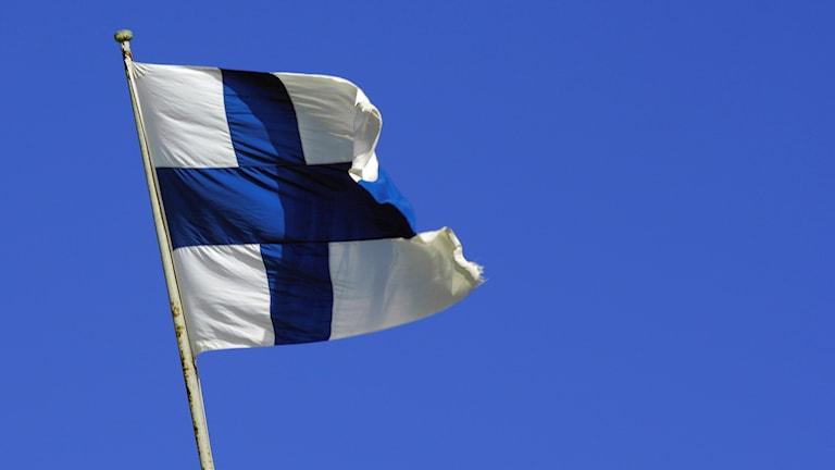 En bild på Finlands flagga mot en blå himmel