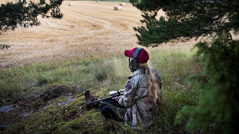 Genrebild på en kvinnlig jägare sitter och blickar ut över ett fält