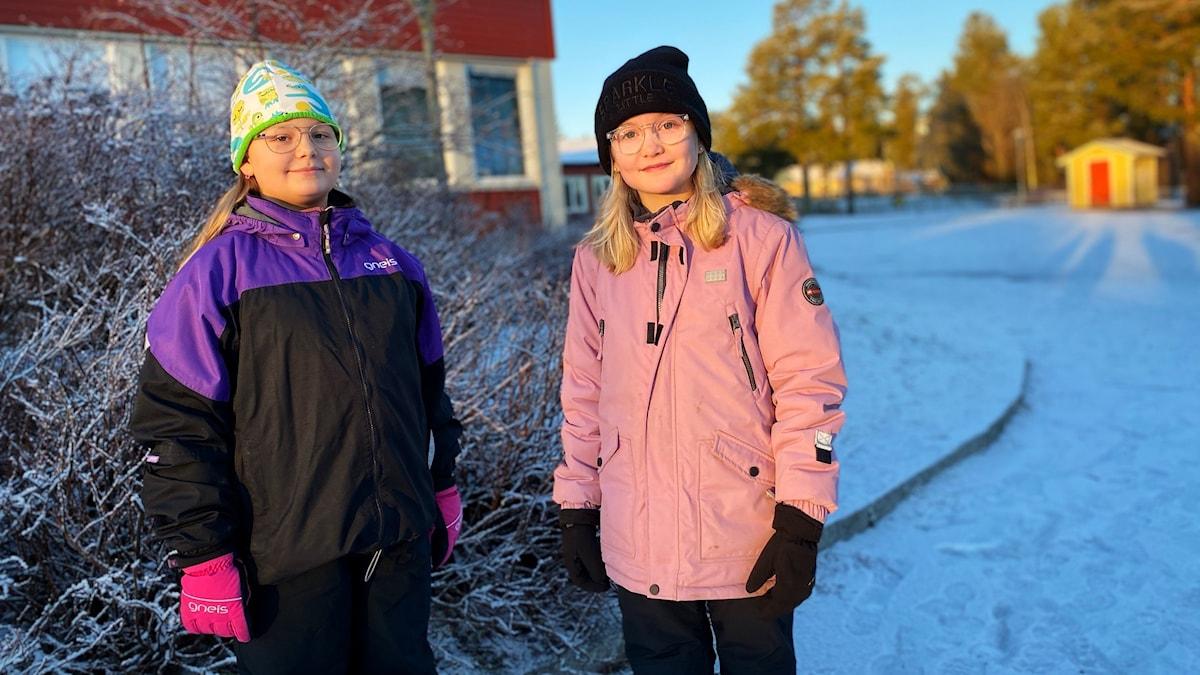 Porträtt av fjärdeklassarna Ottilia Dahlin och Rut Fjellner ute på frostig skolgård i Obbola.
