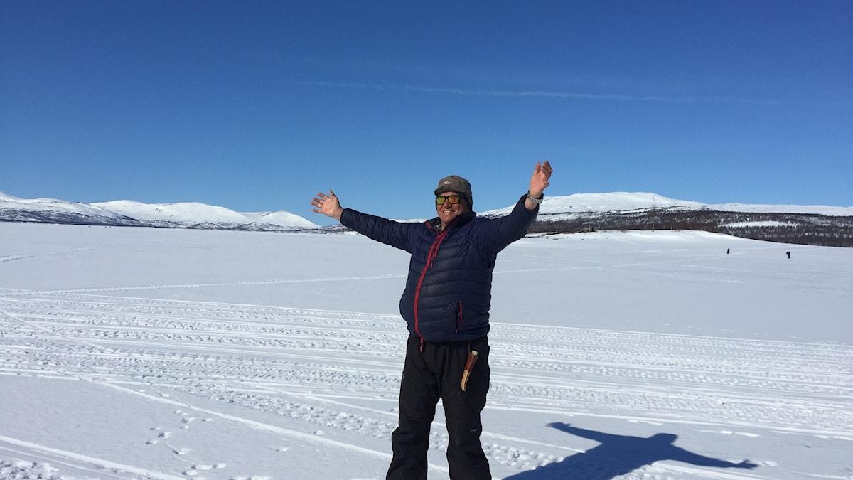 Anders Pärson på står på sjön Överuman med utsträckta armar i solsken och blå himmel.