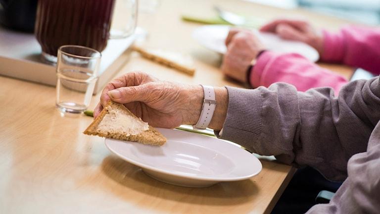 En äldre på ett boende håller i en macka