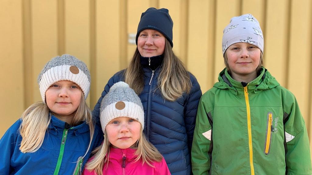 Anna Lundbäck med barnen Ingrid, Kerstin och Erik Lundbäck. De står utanför sitt gula trähus i färgglada vinterkläder.