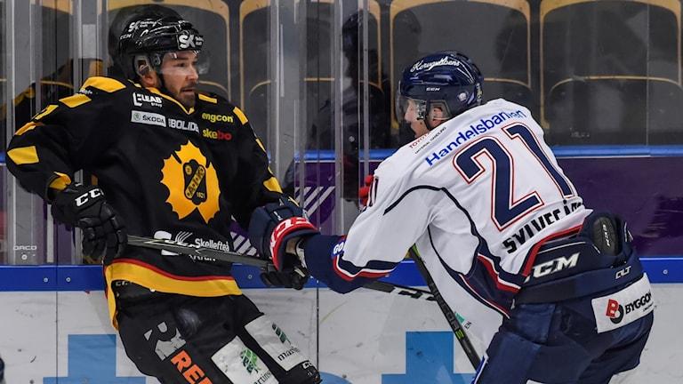 Två ishockeyspelare i kamp vid sargen.
