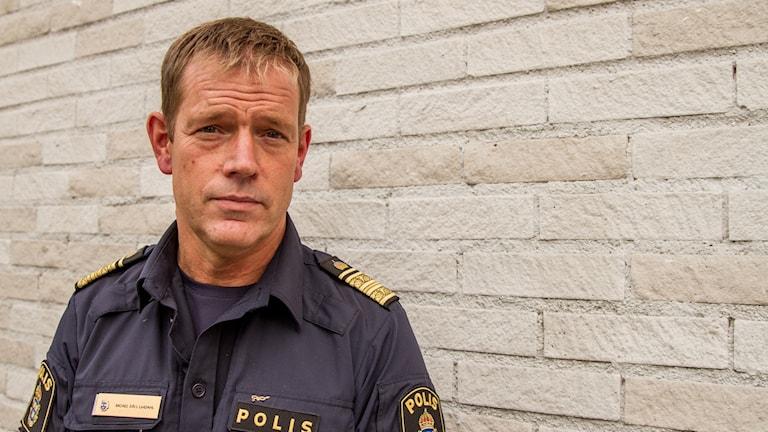 Micael Säll Lindahl, biträdande regionpolischef, framför en tegelvägg