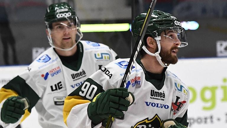 Två vitklädda björklöven spelare med leende på läpparna efter ett mål.