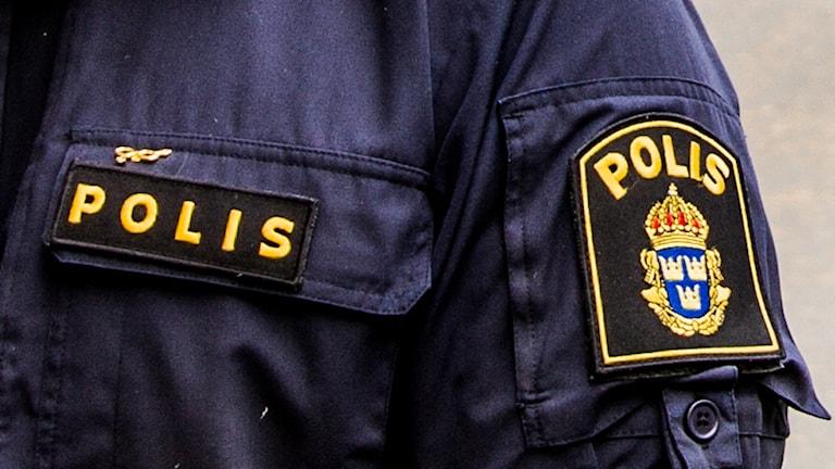 Närbild på polisemblem på en polisuniform