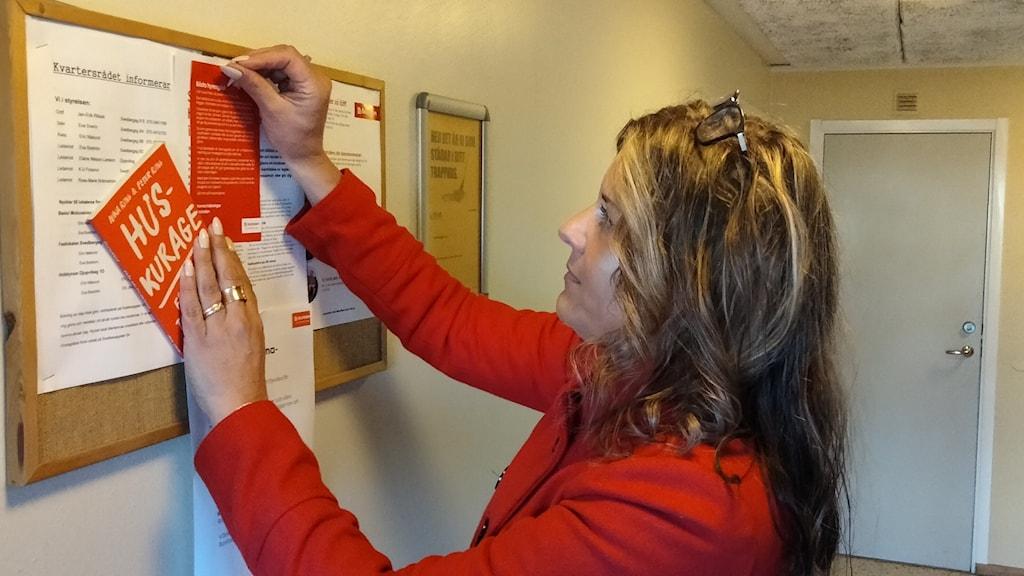 Anna Wiberg, kommunikatör på Bostaden, sätter upp information om huskurrage på en anslagstavla.