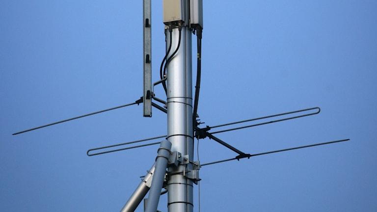 En mobilmast med antenner och mottagare för mobiltelefoni på ett hustak.