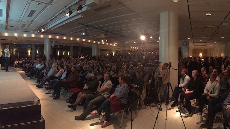 En fullsatt lokal, där människor sitter på stolar framför en scen, På scenene står en man och talar till publiken.