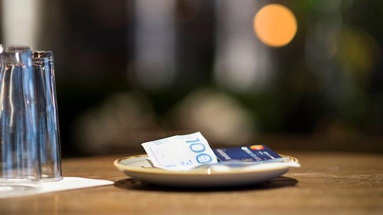 Några sedlar och ett betalkort som ligger på ett fat på ett bord.