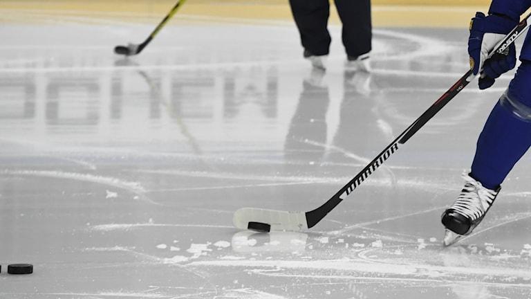 Hockeyklubba ska just skjuta iväg en puck.