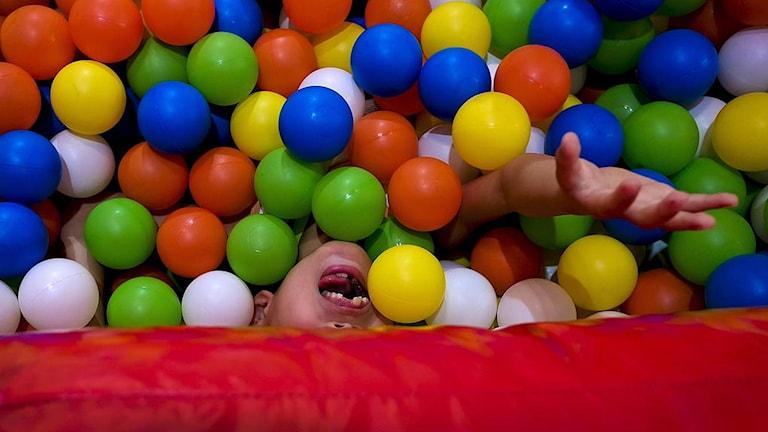 Ett bollhav och ett barn skymtar bland de färgglada bollarna