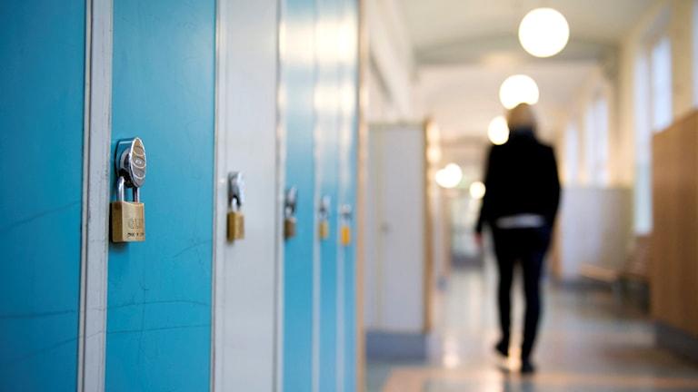 En skolkorridor med blå skåp och en elev som går nedför korridoren