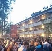 Stor fest på Tvistevägen i Umeå. Människor sitter på taket och dinglar med benen.