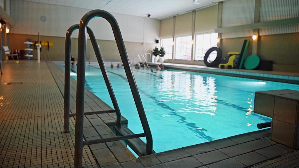 Närbild av stege ner i simbassängen, i bortre änden av rummet syns en grupp äldre i vattnet.