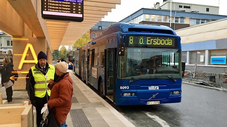 En trafikvärd pratar med en resenär under dagen då Vasaplan i Umeå öppnade efter ombyggnationen