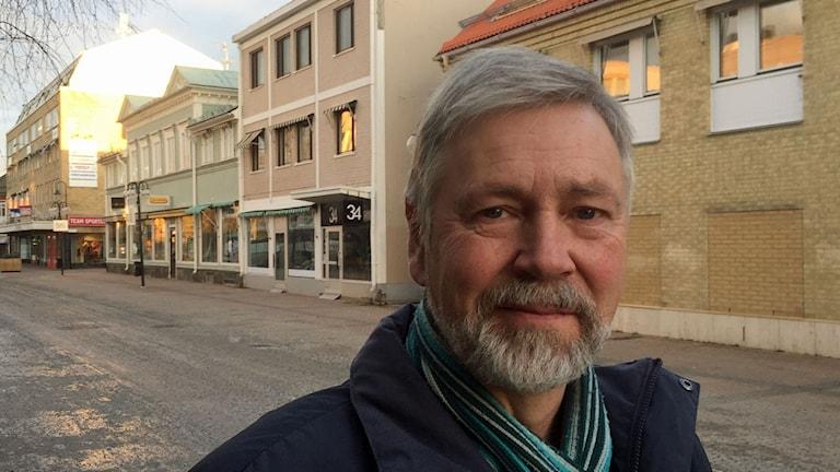 Närbild på en man med grått hår och skägg, framför några av husen längs gågatan i Lycksele.