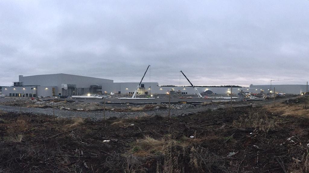 Tre stora grå fyrkantiga byggnader finns synliga i december 2020 av det 8-tal planerade fabriksbyggnaderna.