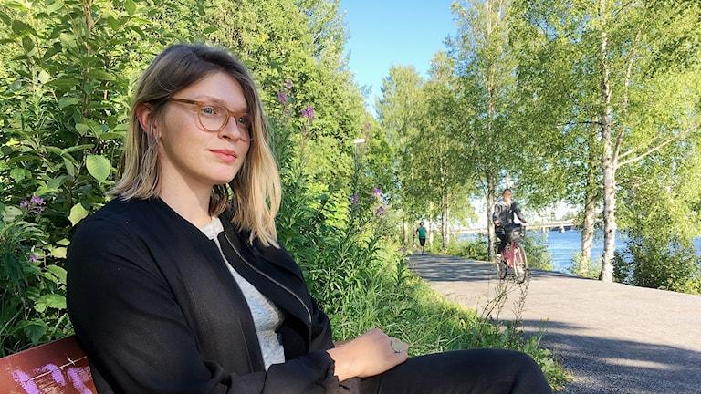 Mi von Ahn på en parkbänk vid en cykelbana vid Umeälven
