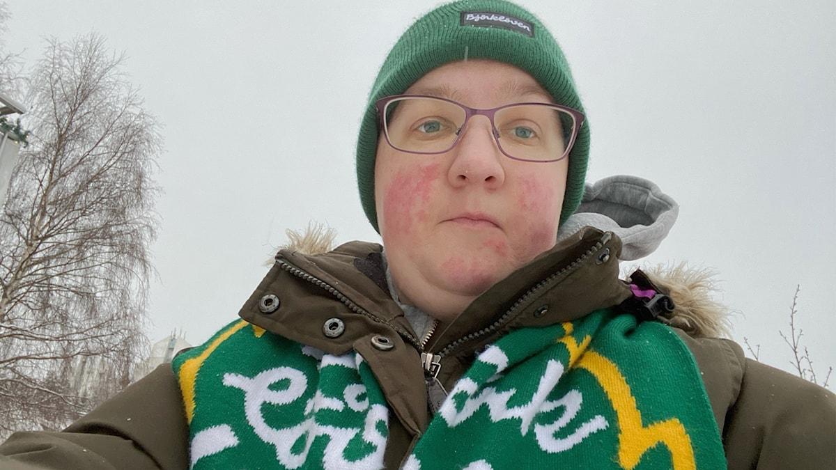 Porträtt kvinna med grön mössa och Björklövens supporterhalsduk. Hon ser samlad eller ledsen ut.