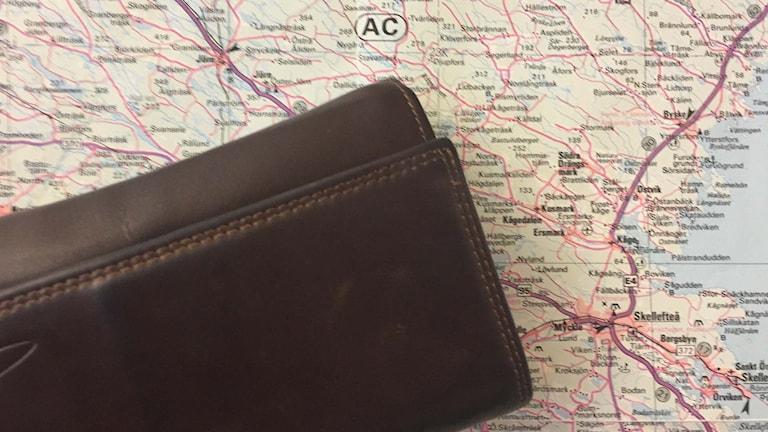 En plånbok ligger på länskartan.