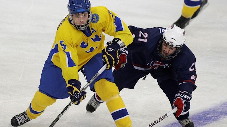 En svensk och en USA hockeyspelare kämpar om pucken