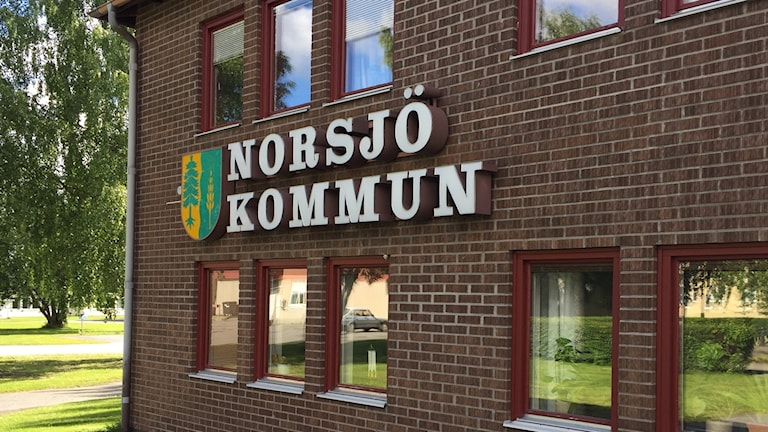 Norsjö kommuns skylt på kommunhusets tegelvägg.