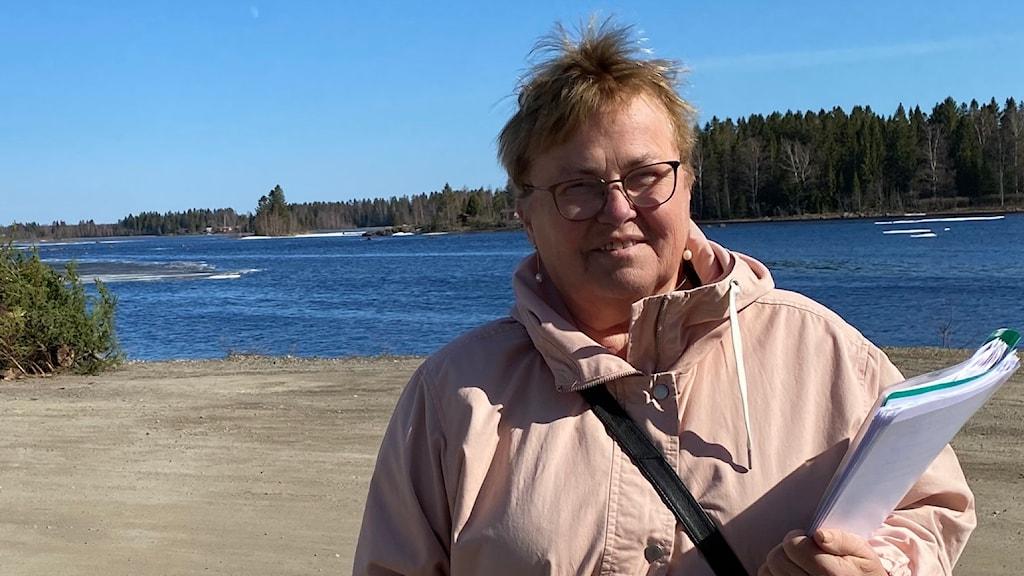 Carin Nilsson, ordförande i Vägföreningen Näckros, håller i namnunderskrifterna. En person står bakom henne med skylt smo varnar för dålig väg.