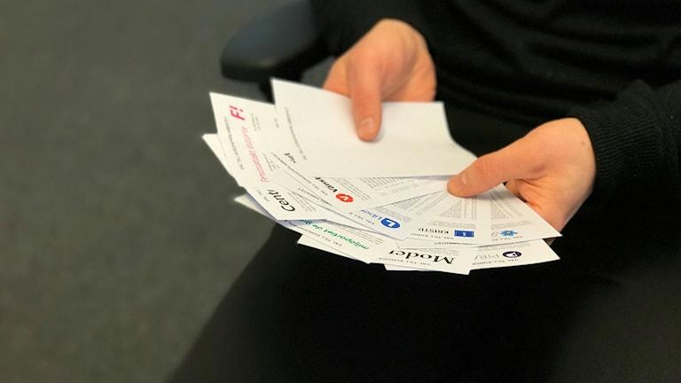 Håller i valsedlar för de olika partierna som kandiderar i EU-valet 2019