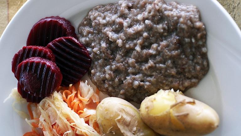 En vit tallrik med rödbetor, pölsa, potatis och sallad