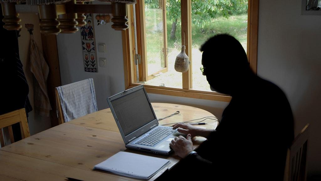 En man sitter med bärbar dator i hemmet.