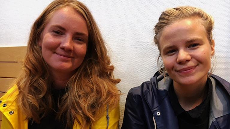 P4s filmkännare Miranda Larsson och Anna Brodin i gul respektive blå regnjacka
